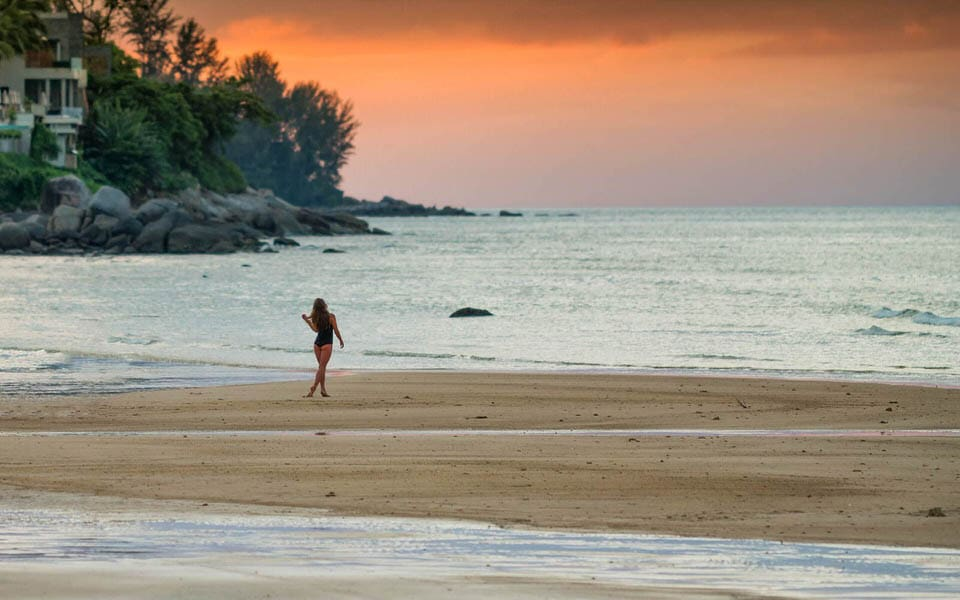 woman walking on the beach during sunset